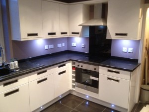Stunning kitchen with LED effect lighting, using reflective surfaces.